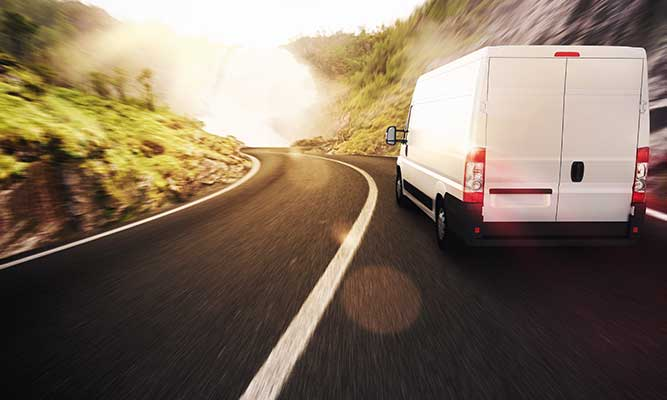 view from behind of a white delivery truck driving around a curve