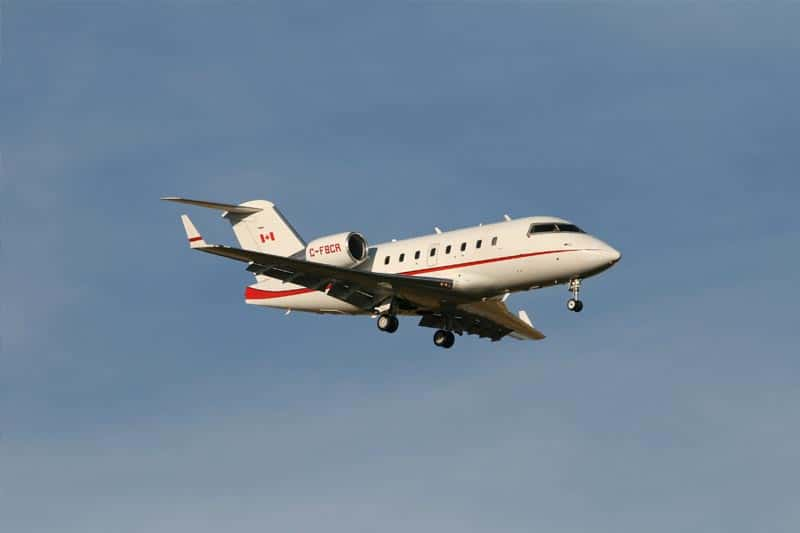 image of a small red and white jet against a blue sky background