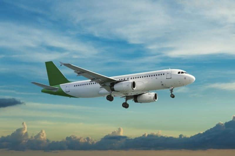 image of an airplane with a green tail flying through the sky