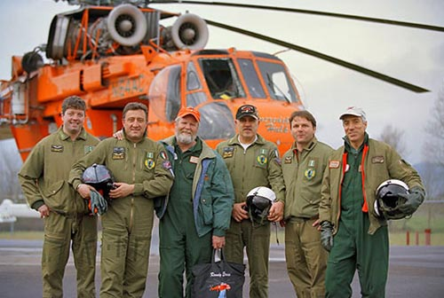 image of 5 men wearing flying uniforms pose in front of a large helicopter