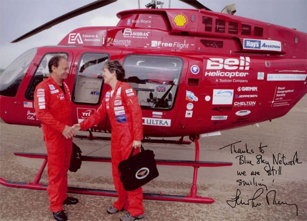 signed image of a woman and man shaking hands in front of a red helicopter