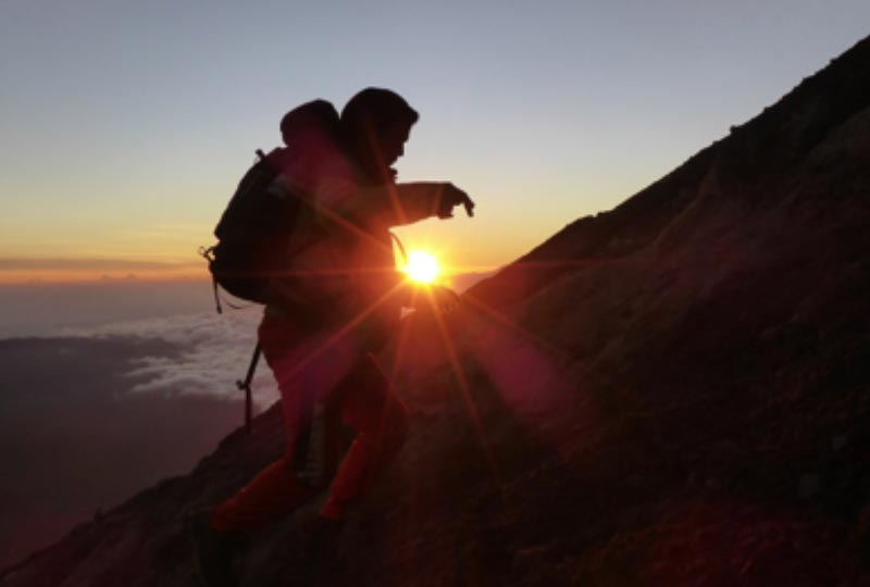 image of a man climbing up the side of a mountain with the sun rising in the background