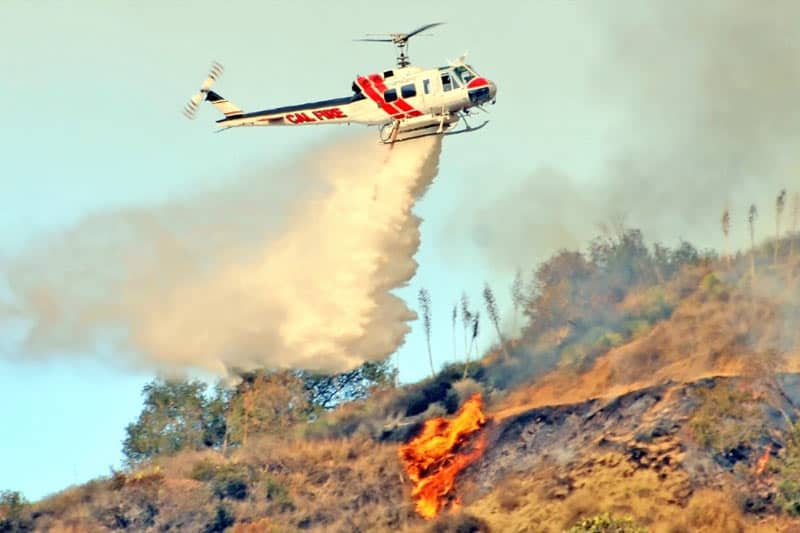 image of a helicopter dumping water onto a fire on the hill below