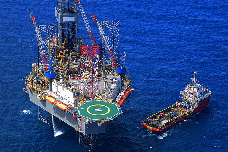 image of an oil platform in the ocean with a red ship next to it