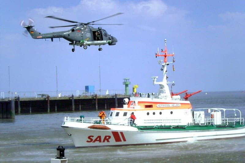 image of a gray marine helicopter hovering over a white search and rescue ship in the harbor
