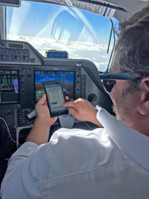 man in cockpit of airplane using a touch screen device